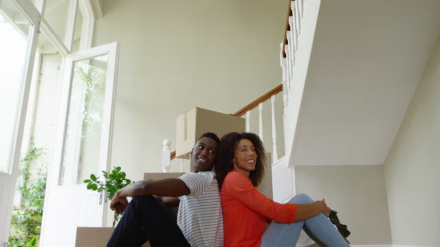 Family moving in to a new home Front view of an African American couple sitting back to back in front of a pile of boxes in the hallway of their new home, resting for a moment while moving in, looking around and smiling, slow motion back to back stock videos & royalty-free footage