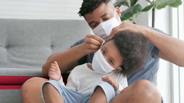 Family of african father tries on a medical mask for his little son on face,stay at home to prevent epidemics of Coronavirus or Covid-19.Father with little boy spending time together.Masks and face coverings (non-Caucasian) video