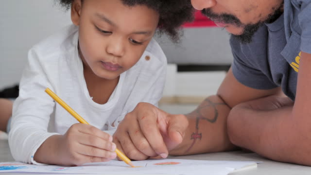 Family of african father with little boy age 2-3 years old while homeschooling stay at home to prevent epidemics of Coronavirus or Covid-19.Young parent father teaching school child boy helps studying at home.Kids and crafts video