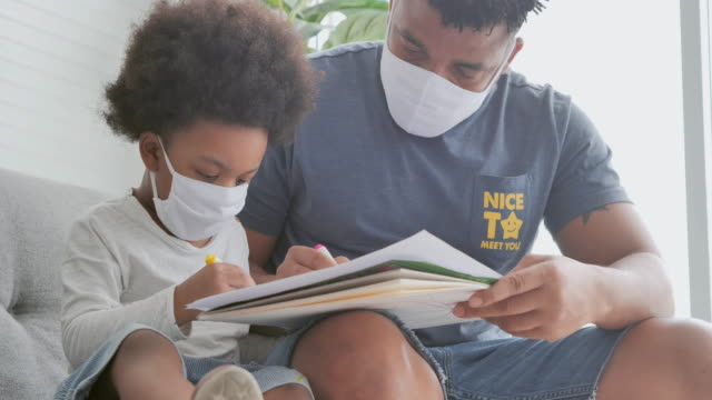 Family of african father with little boy putting medical mask on face while homeschooling stay at home to prevent epidemics of Coronavirus or Covid-19.Father with little boy spending time together.Masks and face coverings (non-Caucasian) - vídeo