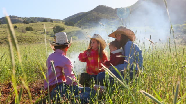 Family of Children Gathered Around a Farm Campfire