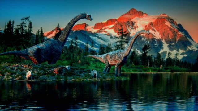 a family of dinosaurs drinking water from a pond - potwór filmów i materiałów b-roll