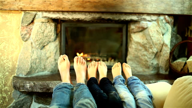 Family of feet warming at a fireplace video