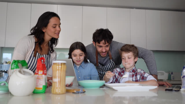 family of four cooking together at home while little girl looks at the recipe on tablet all smiling - пара человеческие взаимоотношения стоковые видео и кадры b-roll
