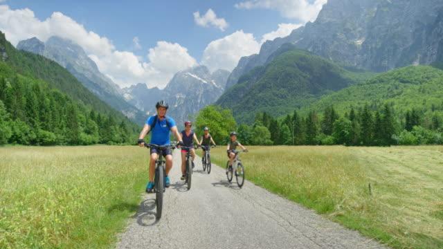 vídeos de stock, filmes e b-roll de família de cs de quatro que andam de bicicleta em um vale bonito da montanha - atividade