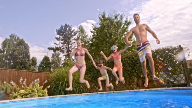 vídeos y material grabado en eventos de stock de familia de cuatro hacer señal con el pulgar de aprobación bajo el agua en la piscina - backyard pool