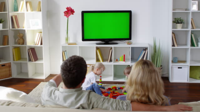 Family of Four Spending Time in Living Room Medium shot with rear view of couple sitting on sofa and talking while watching TV. Little children playing with building block on living room floor family watching tv stock videos & royalty-free footage