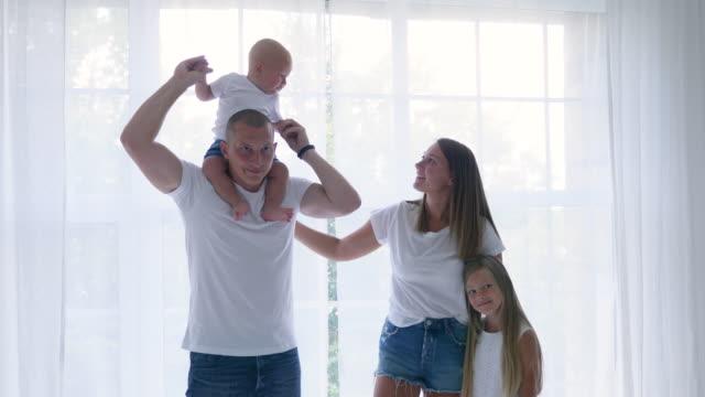 famille de quatre se tient dans une pièce blanche contre - Vidéo