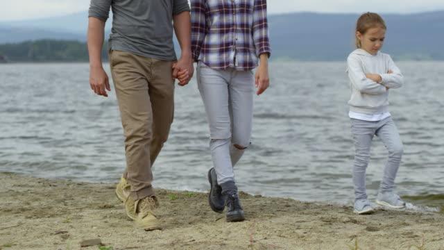 family of four walking along lake shore - four seasons filmów i materiałów b-roll
