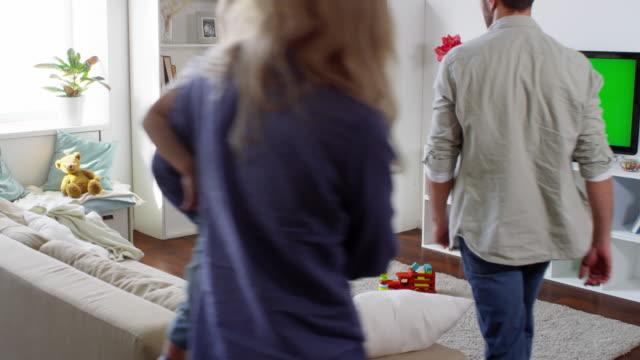 familj på fyra tv-tittande i vardagsrummet - kvinna tillfreds bildbanksvideor och videomaterial från bakom kulisserna