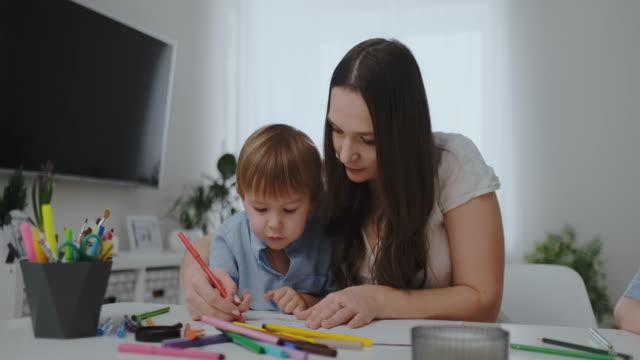 una famiglia di un bambino e una giovane madre seduta al tavolo disegna su carta con matite colorate. sviluppo della creatività nei bambini. interno bianco pulito - matita colorata video stock e b–roll