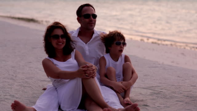 family of three close on a tropical beach video