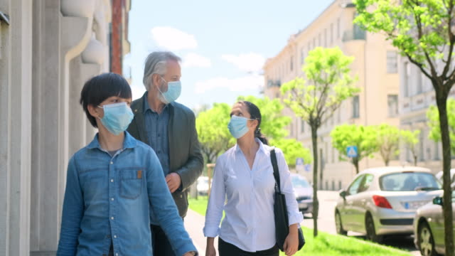 Family of Three Wearing Masks Outdoors During 2020 Pandemic video
