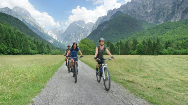 CS Family of three with a teenage son cycling in a green mountain valley Wide crane shot of a man, woman and their teenage son cycling down a beautiful green mountain valley on a nice sunny day. Shot in Slovenia. mid adult women stock videos & royalty-free footage