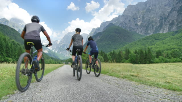 CS Family of three with a teenage son cycling up the green mountain valley Wide crane shot of a man, woman and their teenage son cycling up a beautiful green mountain valley on a nice sunny day. Shot in Slovenia. mid adult women stock videos & royalty-free footage