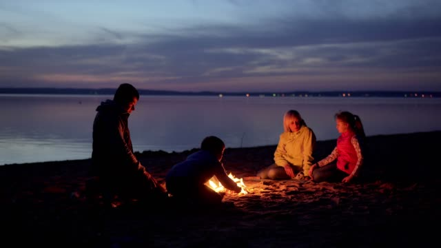 family of tourists resting at campfire on night beach by sea - falò spiaggia video stock e b–roll