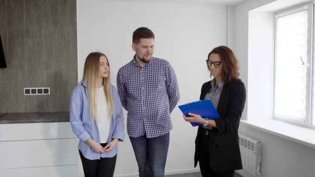 Family of two and real estate agent discussing contract indoor
