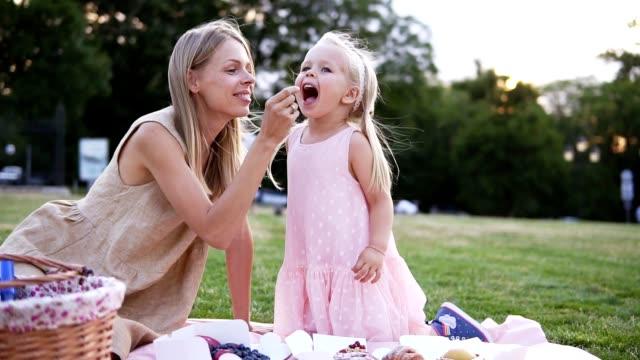 Eine zweiköpfige Familie, eine Mutter und eine kleine Tochter, verbringt die Zeit zusammen in einem Stadtpark bei einem Picknick. Junge Frau und kleines Mädchen essen Süßigkeiten, sitzen auf einer Decke. Mutter füttert ihr Kind spielerisch – Video