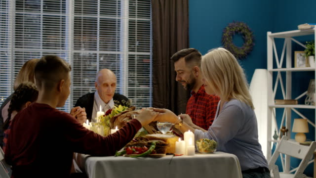 Family offering prayers before Thanksgiving meal Family with children and senior generation sitting at table with candles and meal for Thanksgiving and praying all together at home gratitude stock videos & royalty-free footage