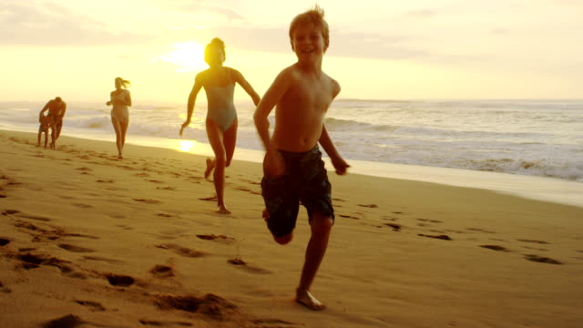 Family on a tropical beach vacation to Hawaii A family together running on the beach on a tropical vacation in a location like Kauai, Maui, Hawaii, Fiji, Tahiti, or the Carribean during an amazing sunset. holiday stock videos & royalty-free footage