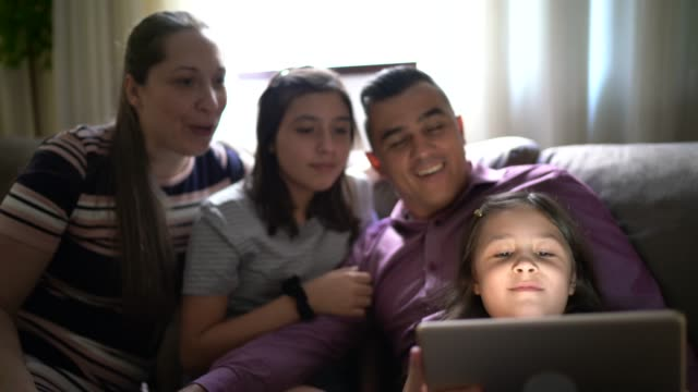 Family on a video call with a digital tablet at home video
