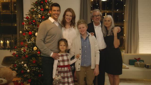 familie an weihnachten vor dem weihnachtsbaum - fotografisches bild stock-videos und b-roll-filmmaterial
