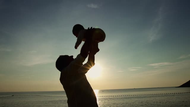 Family on the beach concept, Caucasian father playing and carrying his son on the tropical beach in the sunset.