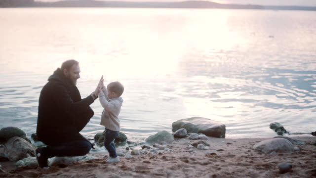 Familia en la costa. Hijo dar cinco a padre, hija corriendo cerca del agua con papá y darle cinco también - vídeo