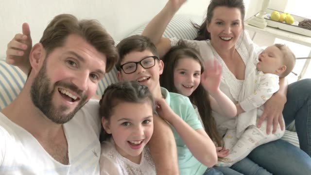 family on video call selfie waving to camera - video call with family video stock e b–roll