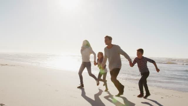 冬の浜辺手とカメラに向かって実行している家族 ビデオ