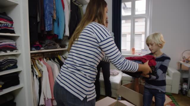 vídeos de stock e filmes b-roll de family organizing closet and donating clothes - economia circular