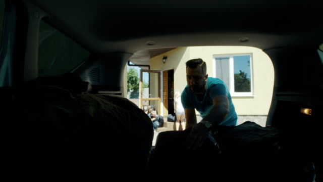 Family packing bags in car trunk