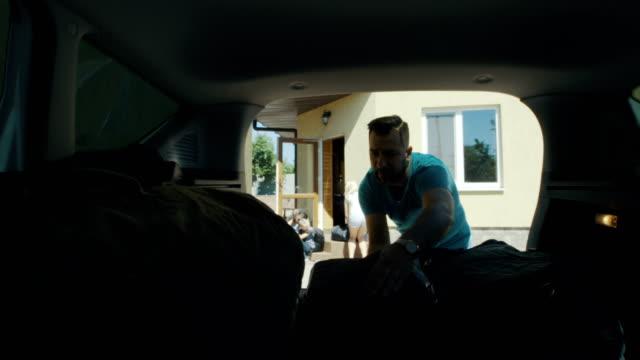 vídeos de stock e filmes b-roll de family packing bags in car trunk - carregar