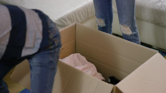 vídeos de stock e filmes b-roll de family packing clothes into boxes and carrying them away - economia circular