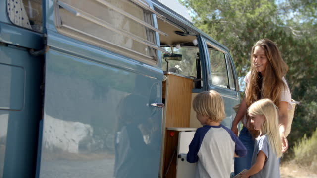 Family packing up their camper van for a road trip vacation video