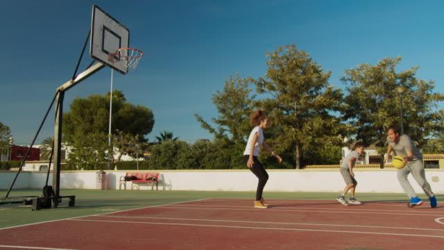 familj spelar basket på sportsground - naturparksområde bildbanksvideor och videomaterial från bakom kulisserna