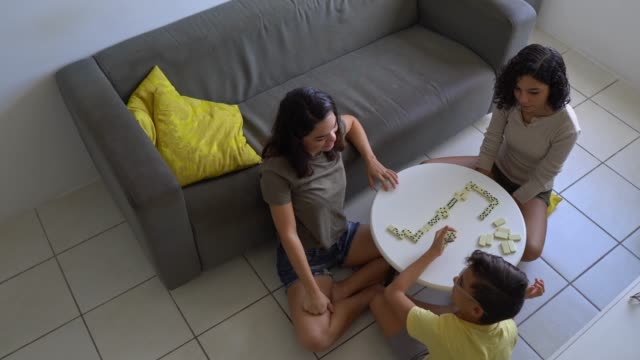 Family playing dominoes at home