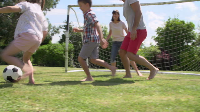 Family Playing Football In Garden Together video