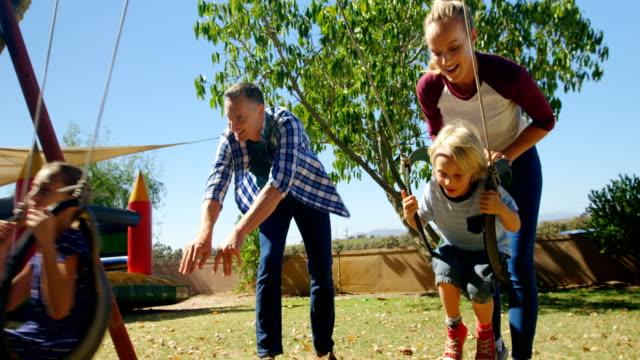 vídeos de stock e filmes b-roll de family playing in the playground 4k - parque público
