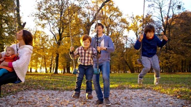 slo mo familie spielen auf der schaukel im park - kind schaukel stock-videos und b-roll-filmmaterial