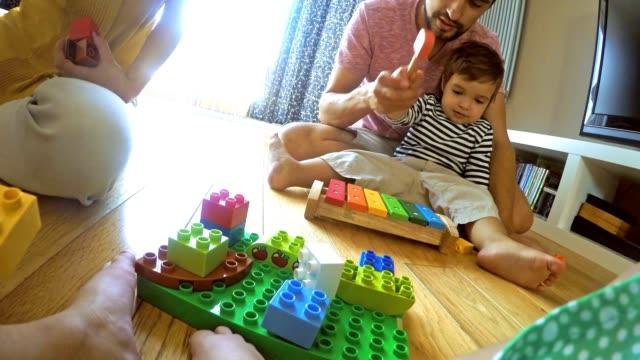stockvideo's en b-roll-footage met pov familie spelen op de woonkamer vloer - baby toy