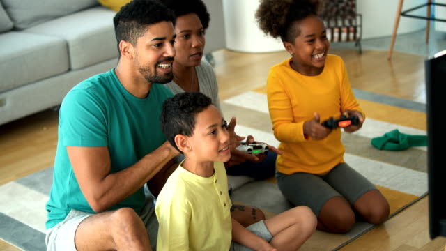 Family playing video games at home. Closeup side view of a young african american family with two children spending time at home during coronavirus pandemic in 2020. They are playing some video games in the living room. Handheld. For later use this is a quite useful family lifestyle footage. video game stock videos & royalty-free footage