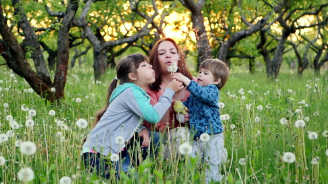 Family Playing With Dandelions In the Garden