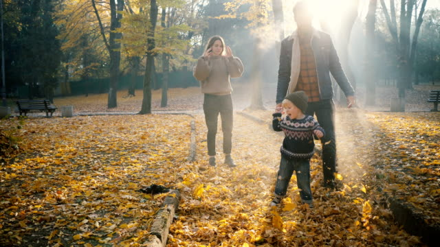 Family  playing with little son in park in autumn