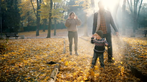 Family  playing with little son in park in autumn Young Caucasian mother and father  playing with little son in park in autumn family stock videos & royalty-free footage
