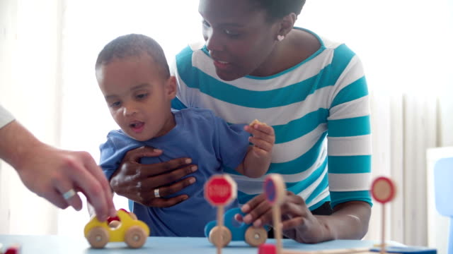 Family playing with wooden toy cars at home. video