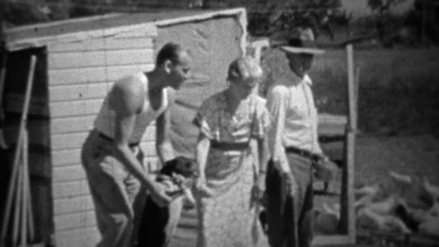1934: Family plays with dog while man casually feeds chickens.