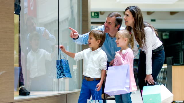 Family pointing at a window at the shopping center video