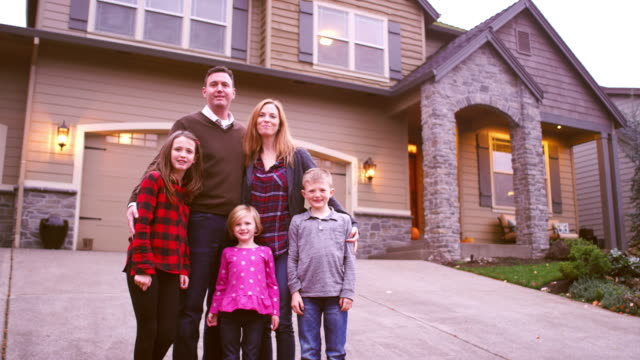 A family poses for a portrait in front of their house video