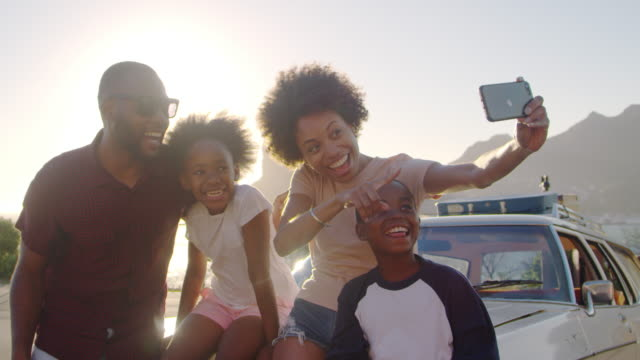 family posing for selfie next to car packed for road trip - vacanze video stock e b–roll